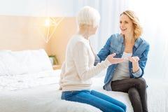 Jovem mulher expressivo que diz uma história surpreendente a sua avó envelhecida curiosa fotos de stock royalty free