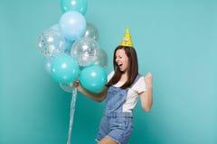 Jovem mulher extático no chapéu do aniversário que grita fazendo o gesto do vencedor, comemoração, guardando balões de ar colorid imagem de stock royalty free