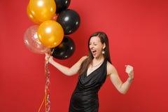 Jovem mulher extático no vestido preto que comemora gritar, fazendo o gesto do vencedor, mantendo balões de ar isolados no vermel fotos de stock royalty free
