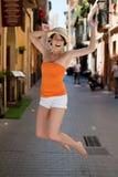Jovem mulher exuberante que salta para a alegria Fotos de Stock Royalty Free