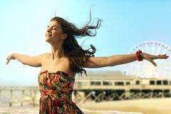 A jovem mulher eyes os braços fechados largamente abertos na praia imagem de stock