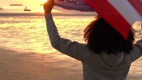 Jovem mulher fêmea do adolescente afro-americano da menina em uma praia envolvida em uma bandeira americana da bandeira dos Estad video estoque