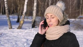 A jovem mulher fala no telefone no parque do inverno, close-up filme