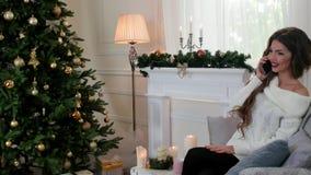 A jovem mulher fala pelo telefone celular na luz solar retroiluminada no assento na sala de visitas em um sofá perto da árvore de filme