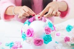 A jovem mulher faz flores artificiais Imagens de Stock
