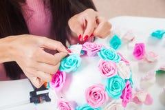 A jovem mulher faz flores artificiais Fotos de Stock