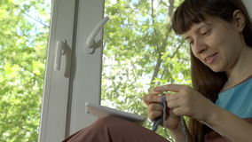 A jovem mulher faz malha do fio azul com as agulhas de confecção de malhas que sentam-se em um peitoril vídeos de arquivo
