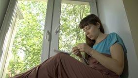A jovem mulher faz malha do fio azul com as agulhas de confecção de malhas que sentam-se em um peitoril video estoque