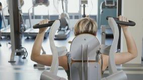 A jovem mulher faz o exercício para a parte traseira no instrumento do treinamento video estoque