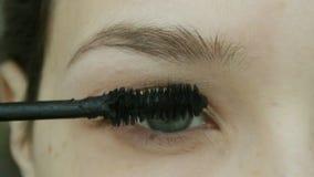A jovem mulher faz o rímel dos chicotes Composição natural do olho em casa filme