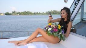 A jovem mulher faz o selfie no iate com grupo da flor nas mãos no resto do verão filme