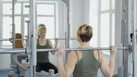 A jovem mulher faz ocupas com o barbell no gym filme