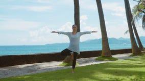 A jovem mulher faz a prática da ioga, relaxando e esticando acima na praia perto do oceano calmo na ilha Bali com fundo bonito vídeos de arquivo