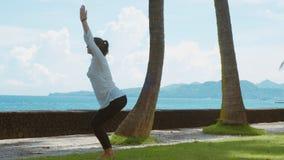 A jovem mulher faz a prática dinâmica da ioga, sol do cumprimento do fluxo do exercício, medita sobre a praia, o fundo bonito e o video estoque