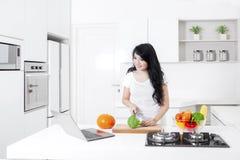 A jovem mulher faz a salada com um portátil fotografia de stock