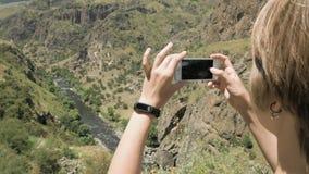 A jovem mulher faz uma foto da garganta nas montanhas - Geórgia video estoque