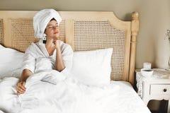 Jovem mulher feliz à moda que relaxa na cama na sala de hotel ou no quarto da casa Menina moreno elegante na toalha branca que ap imagens de stock royalty free