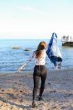 A jovem mulher feliz aprecia o tempo ensolarado e o levantamento na costa do bl fotos de stock