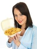 Jovem mulher feliz atrativa que come microplaquetas Imagem de Stock Royalty Free