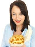Jovem mulher feliz atrativa que come microplaquetas Imagens de Stock