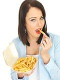 Jovem mulher feliz atrativa que come microplaquetas Fotografia de Stock Royalty Free