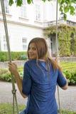 Jovem mulher feliz bonita em um balanço no jardim; impressão Fotografia de Stock Royalty Free