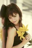 Jovem mulher feliz com as flores que estão na parede na rua da cidade Fotos de Stock Royalty Free
