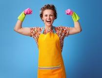 Jovem mulher feliz com as luvas de borracha no azul que mostra o bíceps fotografia de stock