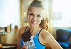 Jovem mulher feliz com a barra de chocolate na sala de visitas moderna foto de stock royalty free