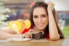 Jovem mulher feliz com câmera do vintage e sobremesa do verão Fotografia de Stock