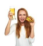 A jovem mulher feliz com a caneca de cerveja da cerveja pilsen e o hamburguer imprensam o hambur Foto de Stock Royalty Free