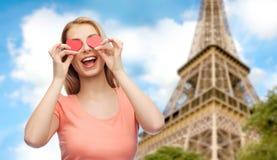 A jovem mulher feliz com coração vermelho dá forma nos olhos Foto de Stock