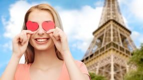 A jovem mulher feliz com coração vermelho dá forma nos olhos Fotografia de Stock Royalty Free