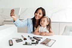 A jovem mulher feliz com filha pequena faz o selfie Fotos de Stock Royalty Free