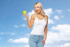 Jovem mulher feliz com a maçã verde sobre o céu azul Imagens de Stock