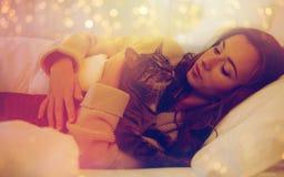 Jovem mulher feliz com o gato que encontra-se na cama em casa Foto de Stock Royalty Free