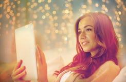 Jovem mulher feliz com o PC da tabuleta na cama em casa Imagens de Stock Royalty Free