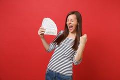 A jovem mulher feliz com olhos fechados que grita, fazendo o gesto do vencedor, guardando lotes do pacote dos dólares desconta o  imagens de stock