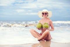 Jovem mulher feliz com os cocos em topless no chapéu de palha com na praia com um coco imagens de stock