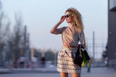 Jovem mulher feliz com sacos de compras que anda ao longo da rua da cidade Imagem de Stock