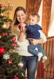 Jovem mulher feliz com seu filho do bebê que decora a árvore de Natal Fotografia de Stock Royalty Free