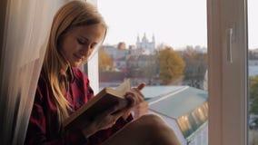Jovem mulher feliz com um livro que senta-se em uma soleira em casa filme