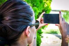 Jovem mulher feliz com um telemóvel imagem de stock