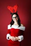 A jovem mulher feliz com vestuário e Papai Noel da rena veste-se no fundo vermelho Fotografia de Stock Royalty Free