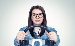 Jovem mulher feliz com vidros e volante do carro, vista dianteira, auto conceito fotografia de stock