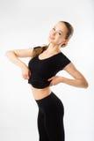 Jovem mulher feliz da aptidão que mostra um estômago liso no sportswear preto imagem de stock