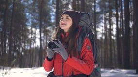 Jovem mulher feliz de sorriso que caminha na floresta do inverno que toma imagens usando o photocamera filme