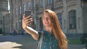 Jovem mulher feliz do gengibre que tem o bate-papo e a posição video na rua com construção no fundo, estudante fêmea de sorriso vídeos de arquivo