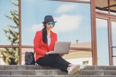 Jovem mulher feliz do moderno que trabalha em outdors do portátil Menina do estudante que usa o portátil no campus universitário  foto de stock royalty free
