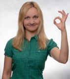 Jovem mulher feliz e sorrindo na camisa verde ocasional que olha em linha reta no sinal da APROVAÇÃO da exibição da câmera fotografia de stock